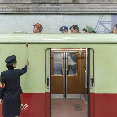 Pyongyang, DPR Korea A metro attendant signals the all clear; Pyongyang. The city's older metro cars were originally imported from West Berlin. Today, domestically produced cars are being introduced.   © Carl De Keyzer - Magnum
